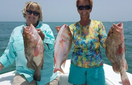 Two women holding Grouper and a Mutton Snapper.